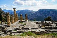 古老废墟世界遗产美丽的景色阿波罗教堂的有绿色橄榄树小树林谷、Parnassus山和蓝色的 免版税库存图片