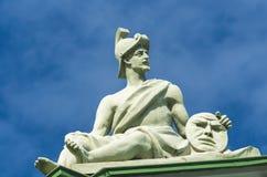 古老战士雕塑坐,并且在手拿着与面孔,面带笑容的一张圈子盘 免版税库存图片