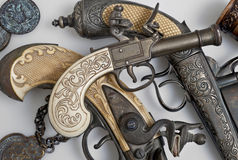 古老手枪和老硬币 库存照片