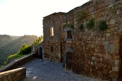 古老日落场面在奇维塔二巴尼奥雷焦,意大利 免版税库存照片