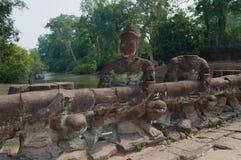 古老桥梁的废墟有邪魔图的吴哥北门的  柬埔寨收割siem 免版税库存照片