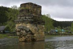 古老桥梁的被毁坏的支持在村庄 库存照片