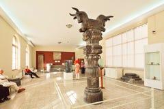 从古老波斯波利斯的被雕刻的专栏和在国家博物馆里面的有些游人 免版税库存照片