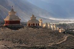古老白色佛教stupas系列与一个红色基地的,决定山的倾斜在落日的光芒, Tibe 免版税库存图片