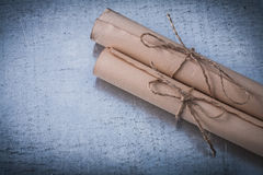 古老的被捆绑的纸在被抓的金属滚动 免版税图库摄影