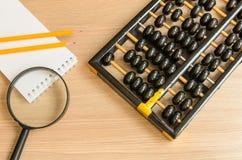 古老算盘,笔记本,铅笔,玻璃 库存图片