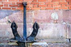 古老船锚在倾斜对墙壁的地面上站立 库存照片