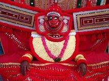 古老艺术影院Kathakali的艺术家衣服和面具的:明亮的红色宽衣物,红色花诗歌选,与ey的金属的红色面具 库存照片