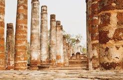 古老被破坏的寺庙Wat玛哈的专栏与石菩萨雕象后面在Sukhothai历史公园的 免版税库存图片