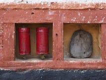 古老西藏祷告在与题字的一块石头附近打鼓伯根地颜色在佛教寺庙的桃红色墙壁的金属表面, 免版税库存图片