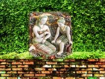 古老雕刻的天使绿色庭院古老砖墙 免版税库存图片
