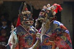 古老面具妖怪和明亮的礼节浴巾的两个和尚执行舞蹈面具在宴餐 库存照片