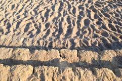 古老黄色石步报道以与波浪的棕色易碎的沙子和不规则性,对海滩的下降 抽象背景异教徒青绿 图库摄影