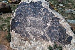 古老刻在岩石上的文字-在石头的驯鹿 免版税库存照片