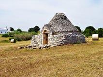 古老Trulli、传统非常老房子有橄榄树的和干草捆在意大利 库存图片