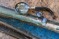古色古香的书脊椎打破与放大器和老玻璃 免版税库存照片