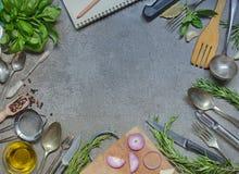 古色古香的利器用调味品、草本和橄榄油在灰色石头 免版税库存图片