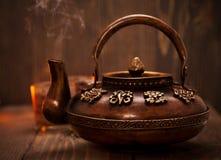 古色古香的在黑暗的木背景的铁热的茶罐 库存图片