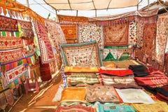 古色古香的地毯的卖主在东方义卖市场市场显示五颜六色的被绣的床罩 库存照片