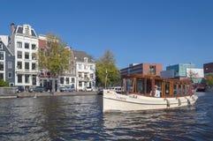 古色古香的小船的上尉有都市风景的在背景 免版税库存照片