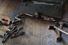 古色古香的工具和工具箱黑暗的木表面上 免版税图库摄影