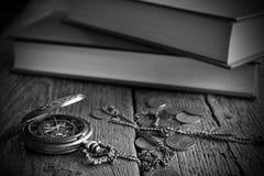 古色古香的怀表、书和老硬币 免版税库存图片
