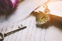 古色古香的怀表和老葡萄酒钥匙与葡萄酒定调子 免版税库存照片