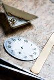 古色古香的手表象限和钟表机构在修理桌上 免版税库存照片