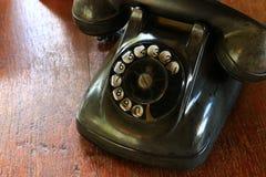 黑古色古香的拨或移动在木桌上的葡萄酒模式电话电话 免版税库存照片