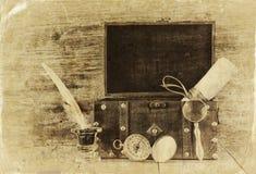古色古香的指南针、墨水池和老木胸口在木桌上 黑白样式老照片 免版税库存照片