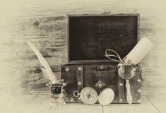 古色古香的指南针、墨水池和老木胸口在木桌上 黑白样式老照片 库存图片