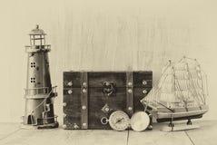古色古香的指南针、葡萄酒灯塔、木小船和老胸口在木桌上 黑白样式老照片 免版税库存图片
