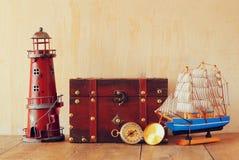 古色古香的指南针、葡萄酒灯塔、木小船和老胸口在木桌上 免版税库存照片