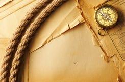 古色古香的指南针和绳索在老地图 免版税库存照片