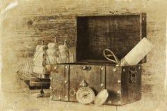古色古香的指南针,原稿,在木桌上的老葡萄酒胸口 黑白样式老照片 免版税库存图片