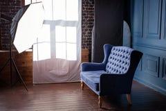 古色古香的木沙发长沙发在葡萄酒屋子里 古典样式扶手椅子在照片演播室用闪电设备 免版税库存图片