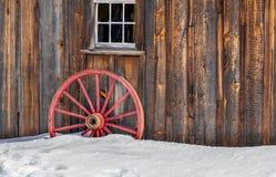 古色古香的木老红色马车车轮雪 免版税库存图片
