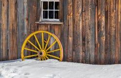 古色古香的木老黄色马车车轮雪 免版税库存照片