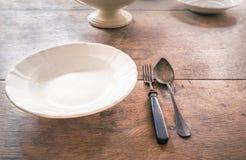 古色古香的板材和碗筷在年迈的木桌上 免版税库存照片