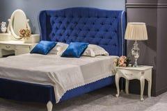 古色古香的样式的豪华皇家卧室与蓝色天鹅绒床和白色nightstand 免版税库存图片