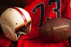 古色古香的橄榄球设备 库存照片