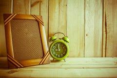 古色古香的照片框架和时钟在木桌上在木背景 图库摄影