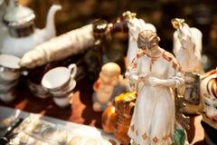 古色古香的瓷妇女小雕象在跳蚤市场上 库存图片