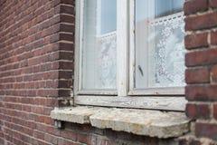 古色古香的白色木窗架、花边窗帘和石窗台在一个深红砖房子 免版税库存图片