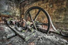古色古香的皮带传动的蒸汽引擎在一家被放弃的工厂 免版税库存图片