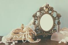 古色古香的空白的维多利亚女王时代的样式框架、香水瓶和白色珍珠在木桌上 减速火箭过滤和定调子 库存照片