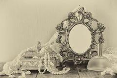 古色古香的空白的维多利亚女王时代的样式框架、香水瓶和白色珍珠在木桌上 黑白样式照片 免版税库存照片
