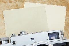古色古香的经典照相机和年迈的照片卡片在难看的东西纸后面 免版税库存照片