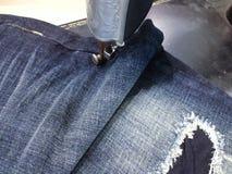古色古香的缝纫机和蓝色牛仔裤 图库摄影