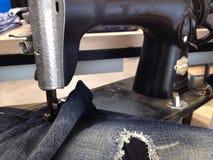 古色古香的缝纫机和蓝色牛仔裤 免版税库存图片